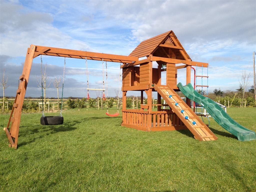 two story playhouse climbing net picnic table monkey bar beam